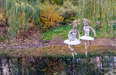 Surreal figures of ballerinas on the lake in a city park.