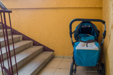 Baby carriage standing on the staircase in the stairwell
