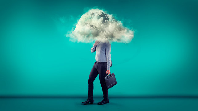 Businessman walking in a blue room with a cloud covering his head.