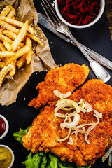 Fried pork chop, French fries and vegetables on wooden background