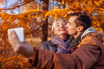 Middle-aged woman taking selfie with her adult son using phone. Family values