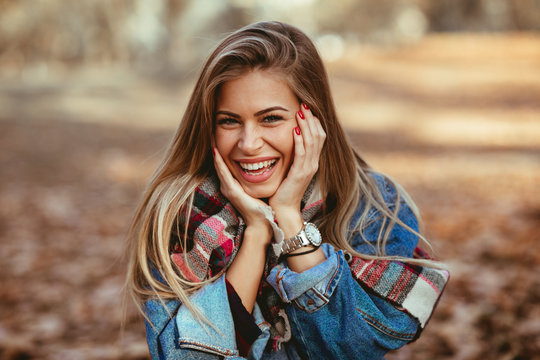 Portrait of a beautiful blonde with a smile on face in the park