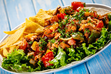 Grilled chicken meat with nachos and vegetables on wooden background