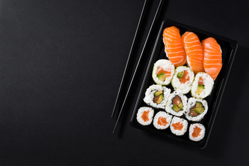 Photo sur Plexiglas Sushi bar Japanese food: maki and nigiri sushi set on black background. Flat lay top-down composition. Copyspace
