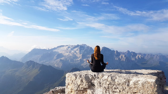 Young woman is practicing yoga at mountain peak