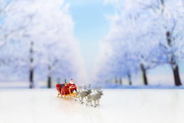 Miniature Santa Claus drive a wagon with a reindeer during the snowfall. Using as concept in Christmas day.