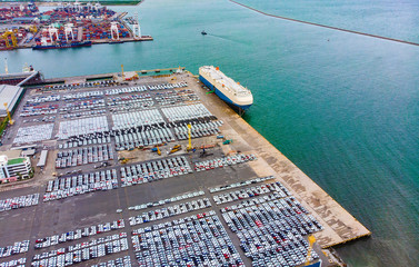 Transportation aerial view from drone top view new cars lined up in the port for import and export.Stock waiting for export