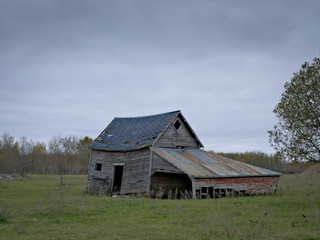 Dreary Abandoned Dilapidated Farm Shed with cloud skies in northern Minnesota