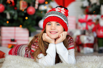 portrait of a beautiful 9-year-old girl in a knitted red hat in a New Year's interior