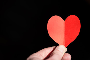 Red heart made from paper in the hand of a young man on a black background.
