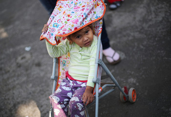 A migrant girl, part of a caravan of thousands travelling from Central America en route to the United States, rests in a makeshift camp in Mexico City