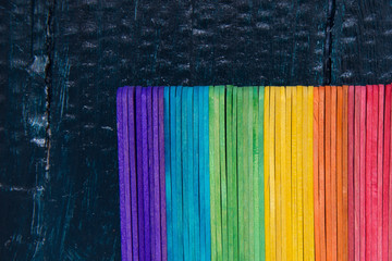 Counting sticks of the rainbow color on a dark blue wooden background.