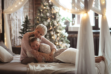 Christmas Mom and teen daughter hugging together