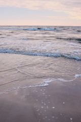Pink sandy Beach. Sea shore scenery with beautiful sand beach. Waves view and cloudscape.