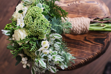 A bridal bouquet of white and green flowers stands on a chair against a wooden floor.