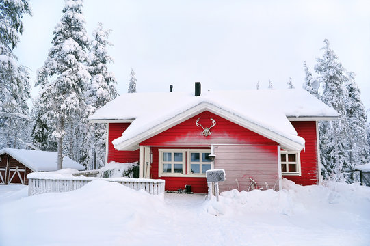 red wooden house in a snow covered landscape