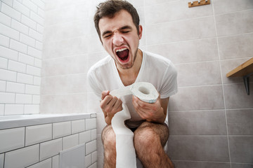The young man has constipation. He sit on the toilet and shouts while holding toilet paper.