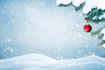 Christmas background with red ornament and falling snow on pine tree branches