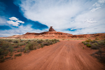 Dirt road trail leads to the Mexican Hat rock formation in the Utah desert. Wide angle