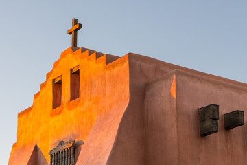 Adobe church and rustic wooden cross glow in golden evening light in Santa Fe, New Mexico