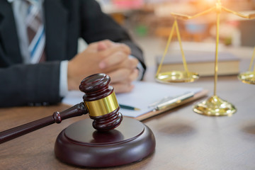 Male lawyer or judge working with Law books, gavel, report the case on table in modern office, Law and justice concept.