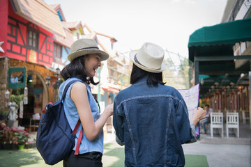Travel Concept. Beautiful girls are happy to travel. Beautiful girls are finding a tourist spot on the map.