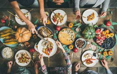 Traditional Thanksgiving day celebration party. Flat-lay of Friends or family eating different snacks and turkey at Festive Christmas table, top view