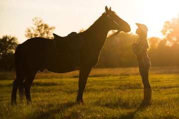 A girl rider stands near a horse and kisses a horse. Horse theme