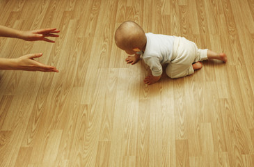 Baby crawling on all fours on the floor to his mother's hands waiting to rais