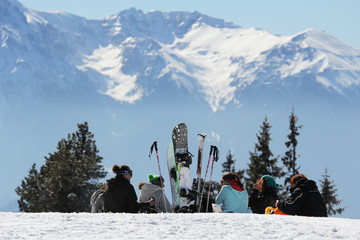 Group of young people with ski, board and skates resting in the top of the mo