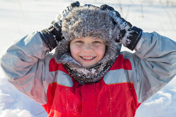 Adorable smiling boy at the snow background