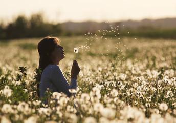 Lady blowing dandelion fluff