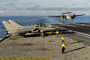 """A picture taken off Toulon shows an E-2C Hawkeye plane landing on the aircraft carrier """"Charles de Gaulle"""", after the completion of its 18 month-long renovation"""