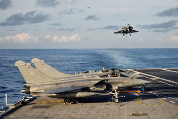 "A picture taken off Toulon shows a Rafale fighter jet landing on the aircraft carrier ""Charles de Gaulle"", after the completion of its 18 month-long renovation"