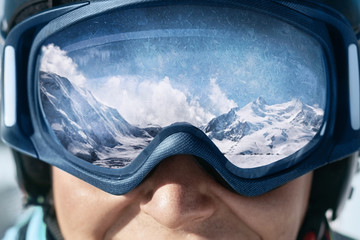 Garden Poster Winter sports Close up of the ski goggles of a man with the reflection of snowed mountains. A mountain range reflected in the ski mask. Man on the background blue sky. Wearing ski glasses. Winter Sports.