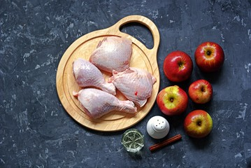 Ingredients for the preparation of baked chicken with apples: chicken pieces, red apples, cinnamon stick, salt, oil. Top view.