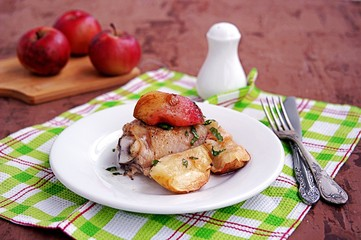 Chicken, baked with apples, on a white plate.