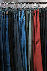 Denim pants in different colors on hangers in a clothing store. The concept of shopping and sales. Background for design on the theme of fashion or second hand.