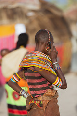 turkana woman wearing the hand made bead traditional jewerly talking on the phone