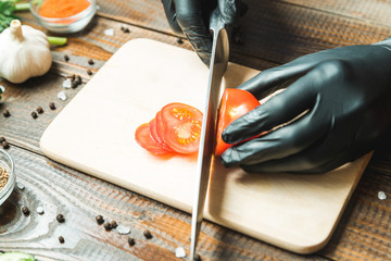 women's hands cut a tomato, next to lie the paprika, herbs, cucumbers and seasonings