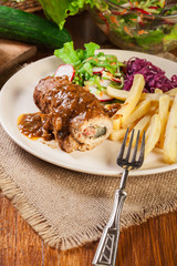 Pork roulade with french fries with salad