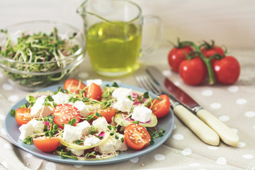 Healthy delicious tasty salad with tomatoes, radishes, cheeses, sprouts and sesame