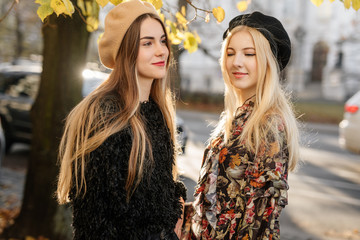 Two pretty girls walk on the city street, talk and smile to each other