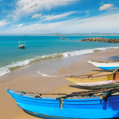 Fishing boat on the sandy shore against a background the ocean and sky.