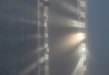 Sunlight reflects from windows of an apartment building on a foggy autumn day in Kiev