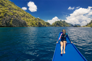 Young woman on the boat and looking forward into lagoon. Travelling tour in Asia: El Nido, Palawan, Philippines.