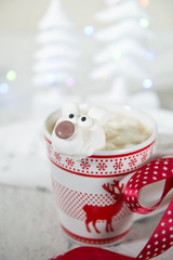 Mug with hot chocolate with polar bear marshmallow face with Christmas trees decorations