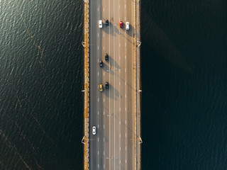 Aerial or top view of bridge with asphalt road or highway over big river with city car traffic, urban transportation