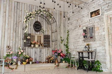 A vintage room  with a iron arch with fake window on a wooden wall and a iron table and chairs on another brick wall surrounded by flowers