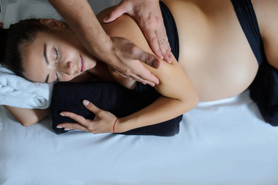 Topview of pregnant caucasian young woman lying on a bed and having a relaxing oriental prenatal massage on her arms